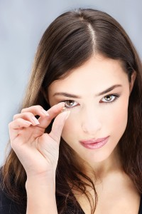 Young woman holding contact lens with two fingers in front of her eye